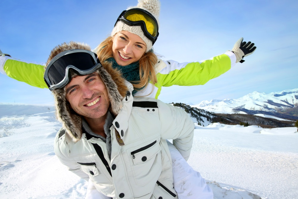 Cheerful snowboarder holding girlfriend on his back_shutterstock